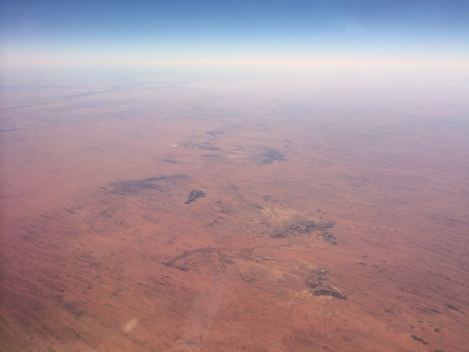 Parallel sand dunes and sporadic outcrops in arid central Australia. Taken from a jet plane.