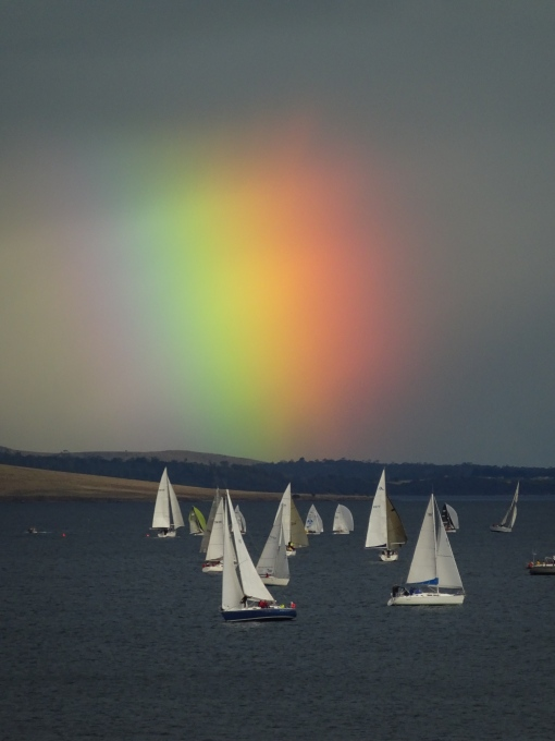 The yachts dance in the wind as the diffuse rainbow behind them lights up the sky.