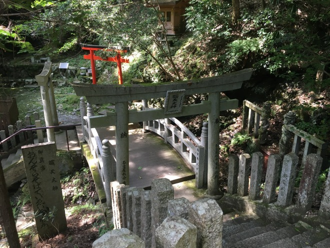 As well as the water sprinkled on the fire, the shrine in a secluded valley west of Kinpusen-ji Temple has a special water source said to promote good health. The temple and shrine are linked by hundreds of steps. Many torii are found along the downhill path. These three are next to a mountain stream that is flanked by two dragon-like images.