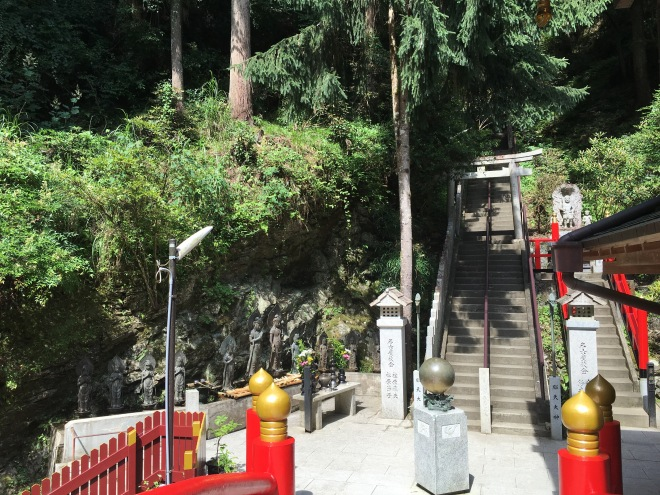 At the bottom of the steps one comes to a vermillion bridge that leads to the shrine. Ladels and water can be found near the statues to partake of Shinto purification ritual before entering the shrine.